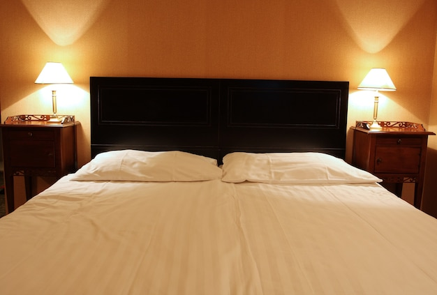 Empty large bed for two with the lamps at the heads