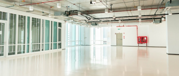 Empty large clean corridor hall space of office with window wall facade, modern white business interior