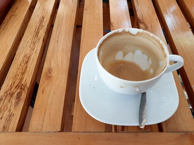 木製のテーブルの上の空のラテコーヒーカップ