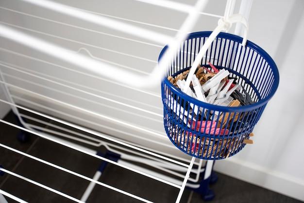 青いバスケットに洗濯バサミが付いた空の洗濯物干しラック、室内の衣類ラック乾燥機