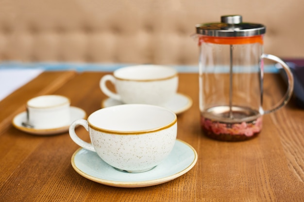 Empty leftover tea cups and teapot on wooden table in cafe or in kitchen at home