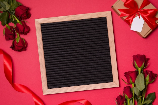 Empty letter board on romanticred valentine's day background with red roses and ribbon.