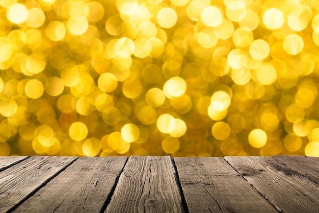空の明るい色の木製テーブルまたは素朴な木の板と、焦点がぼけたぼやけた黄色のお祝いのクリスマスの背景と柔らかいボケ味のライト。背景の配置や製品のためのスペース。