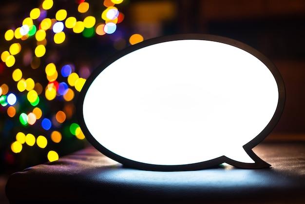 백그라운드에서 화려한 보케 공이 있는 빈 라이트박스 기호입니다. 추가, 판촉, 비즈니스 광고 메시지를 위한 빈 라이트 박스 화면. 텍스트용 흰색 화면이 있는 밝은 채팅 램프