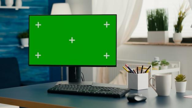 オンラインビデオコール会議用にセットアップされたモダンなクロマキーグリーンスクリーンモックアップコンピューターを備えた空のリビングルーム。誰もいないホームオフィスに隔離されたディスプレイを備えたpc