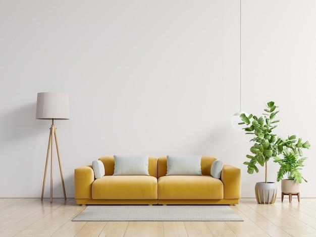 Пустая живущая комната с желтой софой, заводами и таблицей на пустой белой предпосылке стены.