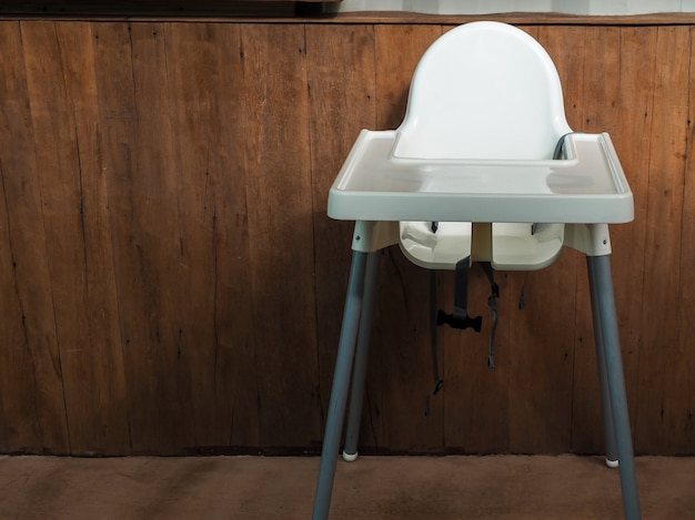 Пустой одинокий старый белый обеденный стул для детей на деревянном