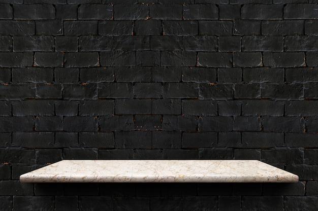 Empty marble board shelf at black brick wall background