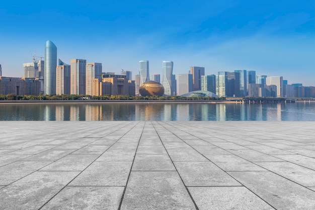 The empty marble floors and the skyline of hangzhou's urban buildings.