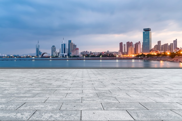 The empty marble floors and the skyline of qingdao's urban buildings.