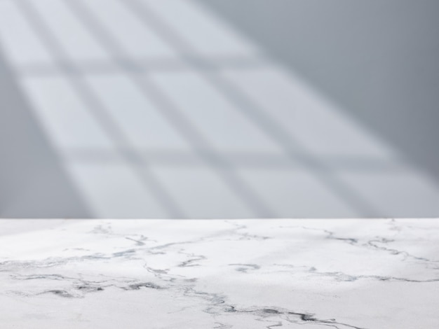 Empty marble table top on wall background with light from window