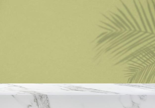 밝은 녹색 질감 벽 제품 배경에 잎 그림자가 있는 빈 대리석 테이블