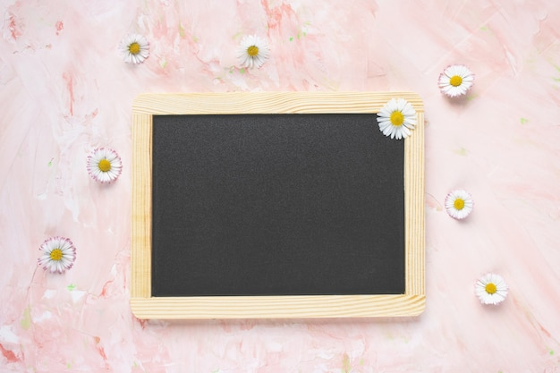 Empty message black board and fresh spring flowers on light pink textured background