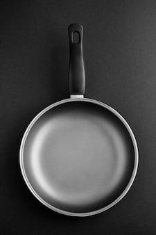 Пустая металлическая сковорода на темноте.