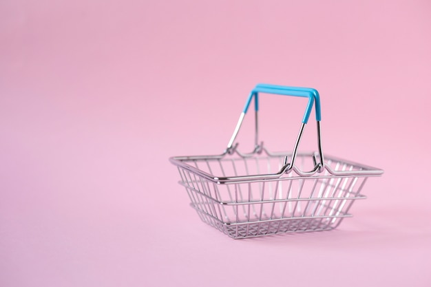 Empty metal shopping basket on pink background, vertical orientation
