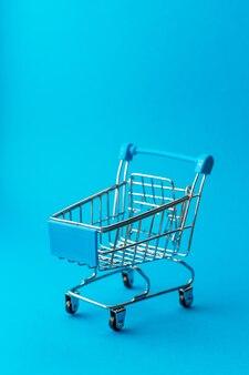 Пустая тележка для покупок металла на голубой стене. скидка и концепция покупок.
