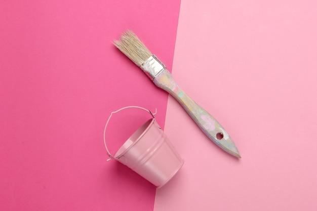 핑크에 빈 미니 양동이와 페인트 브러시. 파스텔 컬러 트렌드.
