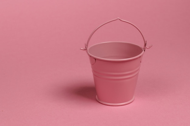 ピンクのパステルカラーの背景に空のミニバケツ。ミニマリズム。トレンドカラーコンセプト