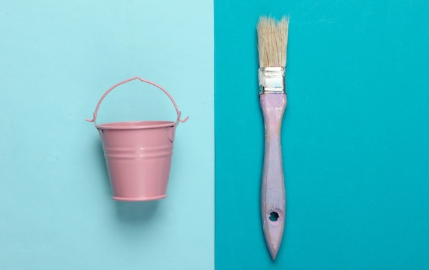 Empty mini bucket and paint brush on blue. pastel color trend.