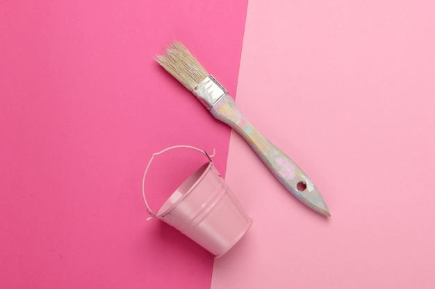 Empty mini bucket and paint brush on pink. pastel color trend.