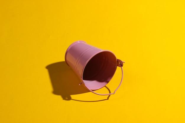 黄色の背景に空のミニピンクのバケツ。影付きのスタジオ撮影