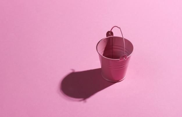 ピンクの背景に空のミニピンクのバケツ。影付きのスタジオ撮影