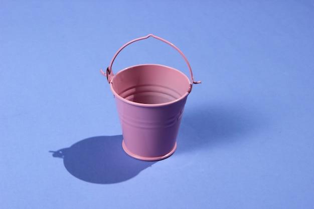 紫の背景に空のミニピンクのバケツ。影付きのスタジオ撮影