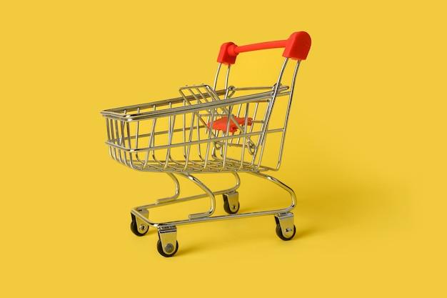 黄色の背景に分離された空のミニ買い物かご。小売。