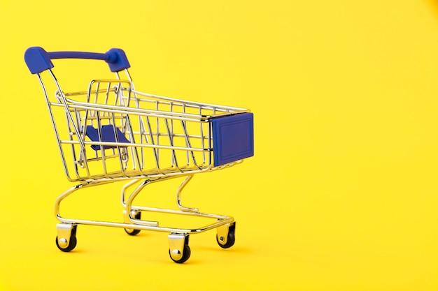 Empty mini shopping cart on yellow background