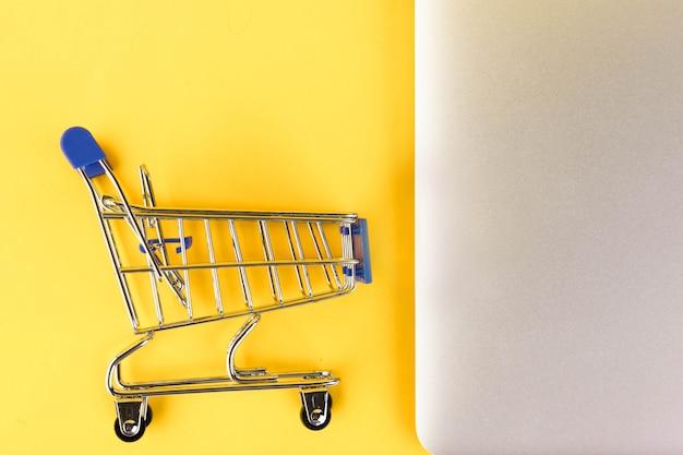 Пустая мини-тележка для покупок, корзина для покупок на желтом фоне. rfi запрос информации. копировать пространство
