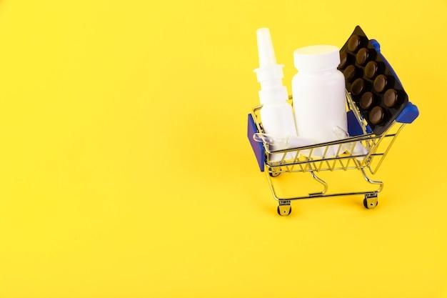 Пустая мини-тележка для покупок, тележка для покупок, корзина с лекарствами на желтом фоне. rfi запрос информации. копировать пространство