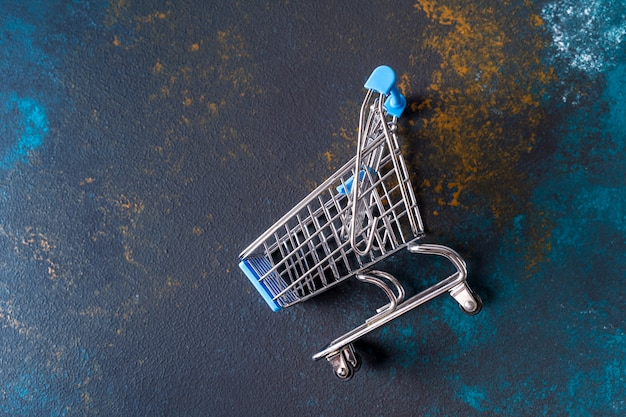 Empty miniature shopping cart on blue concrete background.