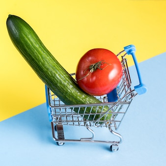 Empty miniature shopping cart loaded with tomato and cucumber on bright blue and yellow surface