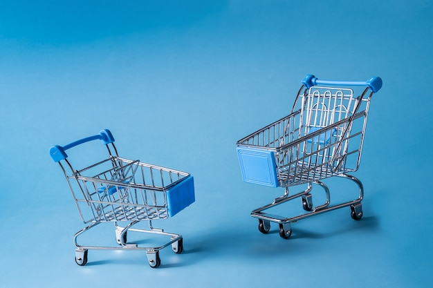 Empty miniature shopping carts on blue background.