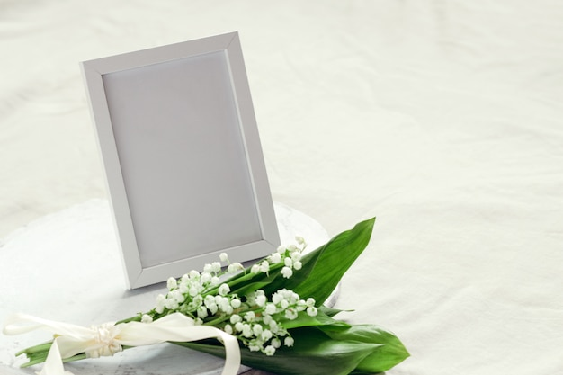 Empty mock up photo frame and bouquet of lilies of the valley