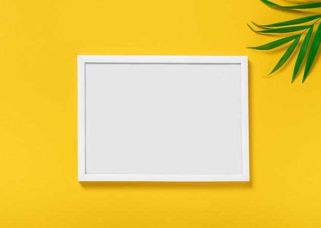 黄色の背景、熱帯のヤシの葉に空のモックアップフォトフレーム
