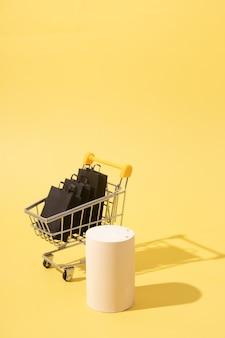 검은색 쇼핑백이 있는 빈 모의 연단 또는 받침대 및 소형 슈퍼마켓 카트