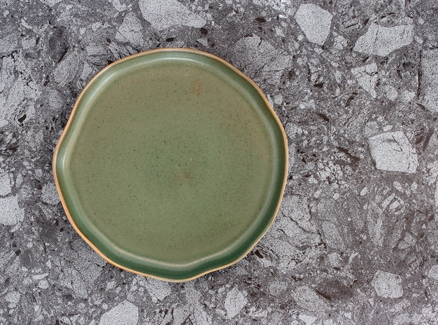 Empty modern ceramic plate on marble table background ,top view
