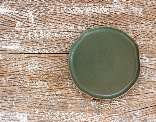 Empty modern ceramic plate on wood table background ,top view