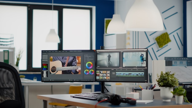 Empty modern creative agency office with dual monitors setup with processing video film montage vide...