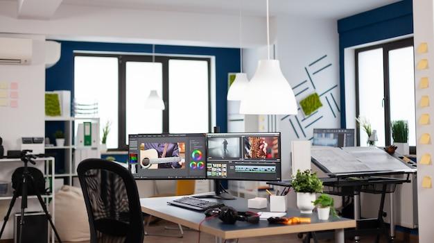 비디오 필름 몽타주를 처리하는 듀얼 모니터 설정이 있는 비어 있는 현대적인 크리에이티브 에이전시 사무실