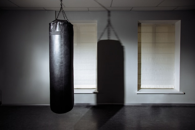 Empty modern fight club with punching bag for practicing martial arts.