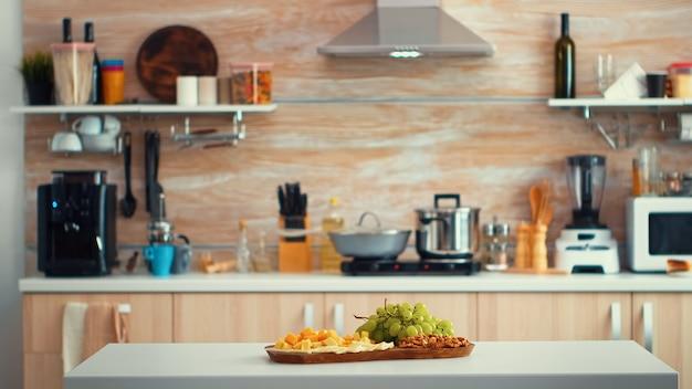 テーブルの上にブドウと空のモダンなキッチン。日光とぼやけた背景のオープンスペースのキッチンルームのインテリア。真ん中にダイニングテーブルを備えた豪華な建築住宅装飾をデザインする