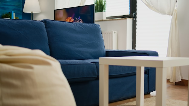 壁に心地よいソファを持っている人がいない、空のモダンなリビングルーム、バックグラウンドとテレビに職場があるエレガントなスタイル。青い壁の誰もいないインテリア、美しい装飾が施されたアパート