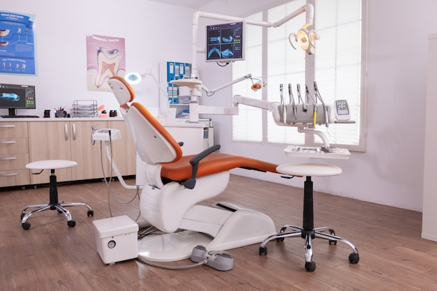 Empty modern teethcare stomatology hospital office with nobody in it equipped with dental intruments ready for orthodontist healthcare treatment. tooth radiography images on display