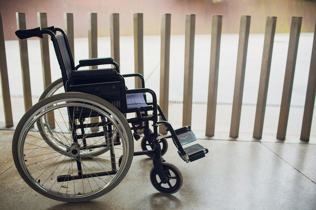 Empty modern wheelchair near brick wall indoors.
