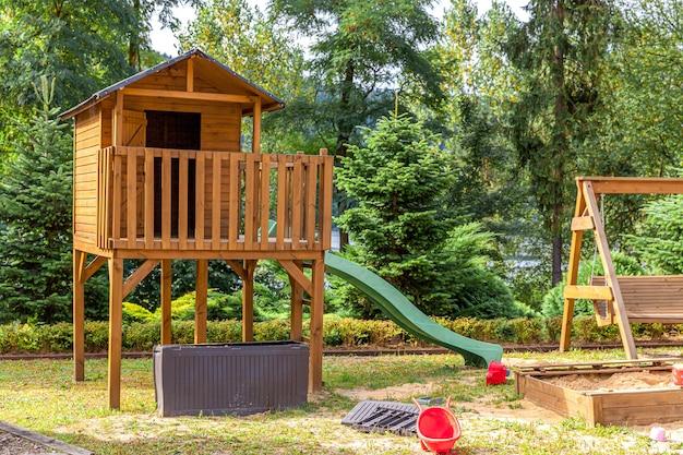 Empty modern wooden children playground set on green yard in public park in summer day.