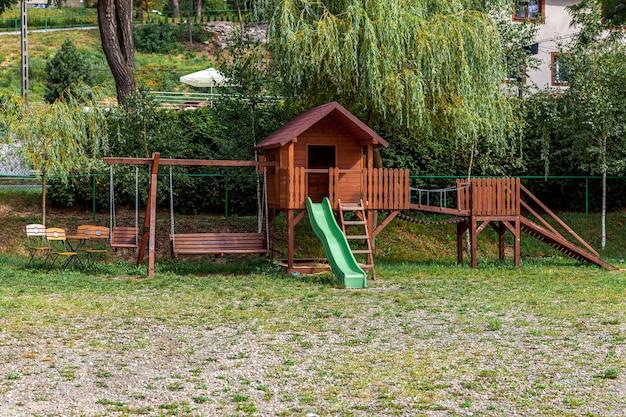 Empty modern wooden children playground set on green yard in public park