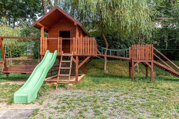 夏の日の公共公園の緑の庭に設定された空のモダンな木製の子供の遊び場。子供のための面白いおもちゃの土地。屋外の子供のための都市運動活動。近所の子供時代のコンセプト。