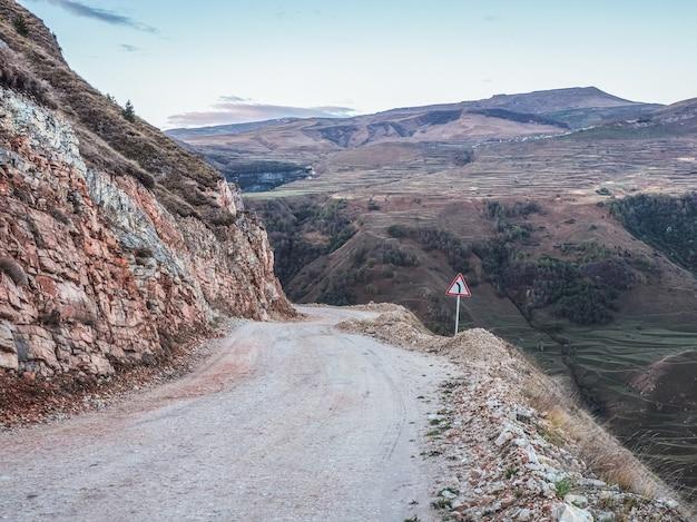 空の朝の危険な狭い崖の山道。山の端と急な崖に沿って運転する危険なオフロード。